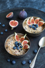Bowls of porridge with sliced figs, blueberries and dried berries