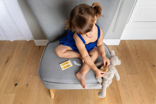 Little girl putting band-aid on plush toy