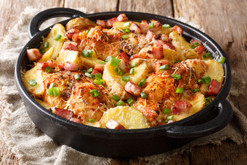 Traditional chicken breast baked with potatoes, bacon and cheese close-up in a frying pan. horizontal