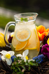 lemonade in a jug on a background of flowers
