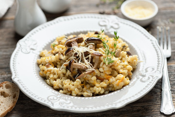 Pearl barley mushroom risotto on wooden table, closeup view, selective focus