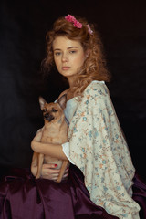 Portrait of a young romantic woman with blond curly hair in a vintage floral dress sitting over black background. Close Up of woman with dog. Heroine of a novel