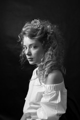 Portrait of a young romantic woman with blond curly hair in a vintage floral dress sitting over black background. Heroine of a novel