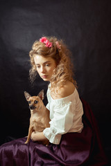 Portrait of a young woman in a vintage dress with a cute puppy on her lap, sitting over black background. Close Up of woman with dog. Romantic girl with blond curly hair