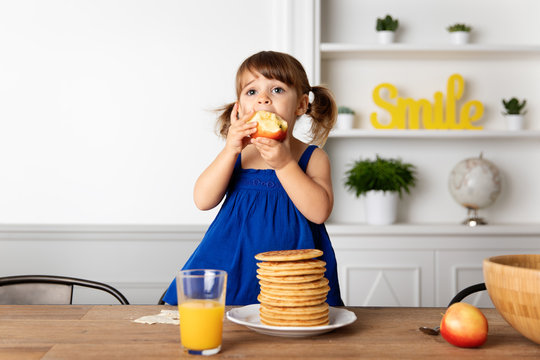 Little girl standing on a chair at breakfast table eating an apple