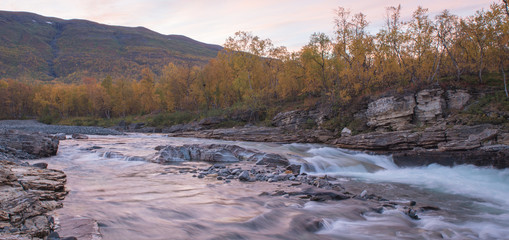 Flowing river landscape in a mountain landscape. Abisko national park in Sweden.