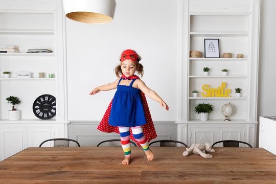 Little girl dressed up as superhero standing on kitchen table