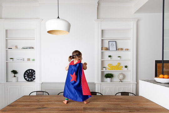 Toddler dressed up as superhero standing on kitchen table