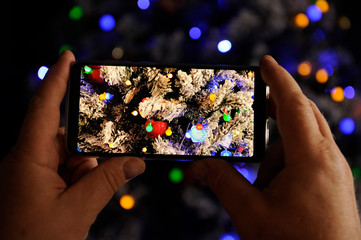 Elderly man holds in his hands new model of  smartphone and take pictures of garlands and Christmas lights on New Year tree. Christmas Eve