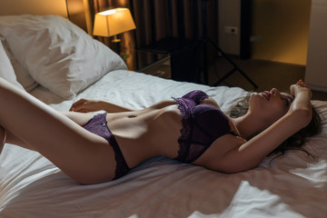 Sexy brunette woman in lingerie relaxing on the bed in the hotel