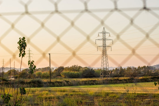 high voltage wires tower industrial concept shot through metal grid fence in village landmark country side environment valley in evening sunset golden colors