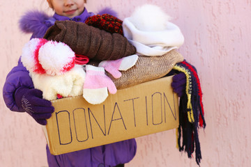 Girl holding donation box with warm winter clothes.