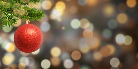 Christmas red ball on the branch. Free space for Christmas, New Year greetings text. Bokeh background.