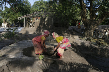 Women work in front of a damaged house after it was hit by a tidal wave on Ghoramara Island