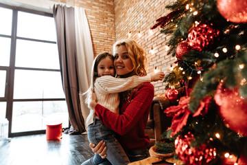 Christmas. Childhood. Home. Little girl and her mom are standing near the Xmas tree, hugging, looking at camera and smiling