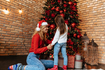 Christmas. Childhood. Home. Little girl and her mom are playing with the Xmas tree and smiling
