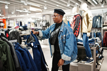 Stylish casual african american man at jeans jacket and black beret at clothes store looking on new jacket.