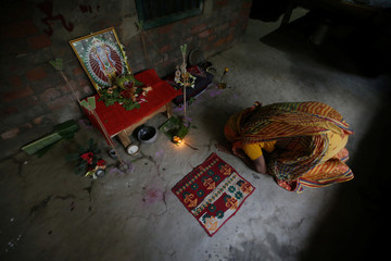 A Hindu woman offers prayers during Laxmi Puja festival on Ghoramara Island