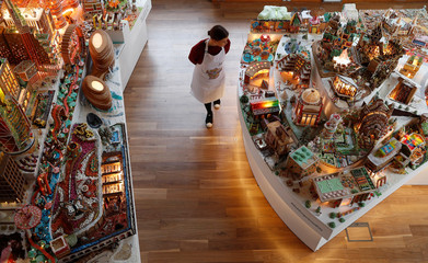 A staff member poses for a photograph next to the Museum of Architecture's Gingerbread City at the V&A Museum, in London