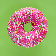 Donut with bright pink icing and multicolored sugar sprinkle with vermicelli on a green background. Minimal geometric color concept.