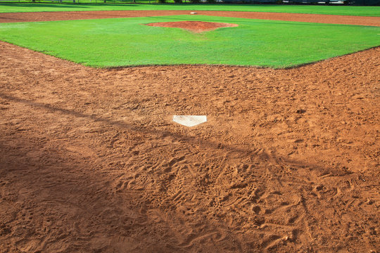 A youth baseball field viewed from home plate in morning light