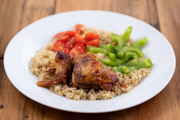 quinoa with chicken and vegetables on white plate