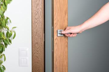 Open the door. A man's hand on the door handle. Dark wood and light interior. Wall mural