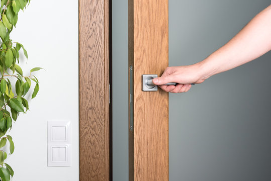 Open the door. A man's hand on the door handle. Dark wood and light interior.
