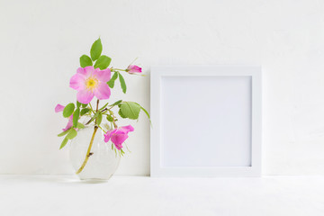 Mockup with a white frame and pink rose hips flowers