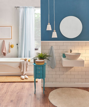 Modern new style bath room, white ceramic and  blue background, sink and mirror, white lamp with carpet. White tub and towel background style with frame.
