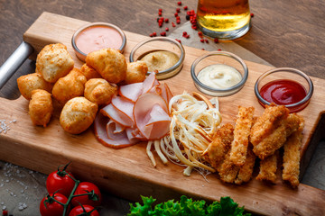 Big set of snacks for beer it includes fried cheese balls, pigtail cheese, ham and crab sticks on a wooden board