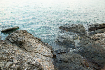 Wide view of rocky shores and calm tides during a blue sunset. Khao Laem Ya, Rayong, Thailand. Travel and nature.