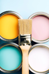 Brush with wooden handle on open cans on blue pastel background. Yellow, white, pink, turquoise...