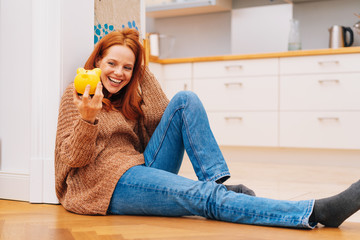 Young woman laughing as she holds her piggy bank