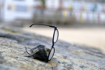 A pair of spectacles lost on the beach are left weighted down on a rock in the hope that the owners may come back and find them.