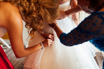 Bride getting dressed by her mother and sister