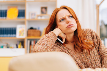 Confused young redhead woman