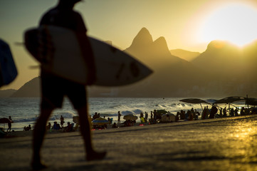 Silhouettes of surfers walking on the Ipanema Beach boardwalk in front of a bright scenic view of the sun setting behind Two Brothers Mountain in Rio de Janeiro, Brazil