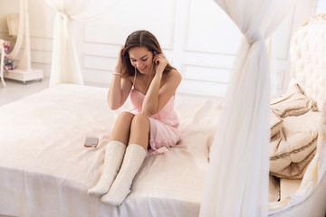 Young woman in a pink dress with headphones listening to music sitting on the bed