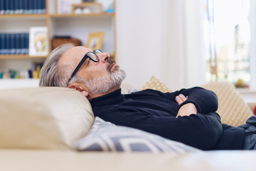Middle-aged man relaxing on a sofa at home