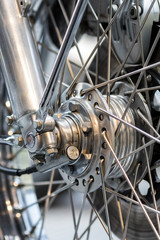 Engineered motorcycle wheel parts. Disc brake suspension and spokes. Complex engineering close-up.