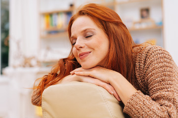 Blissful young redhead woman sitting daydreaming