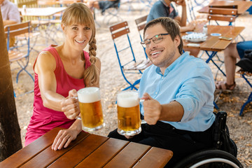 Disabled man in wheelchair and friend drinking beer clinking glasses