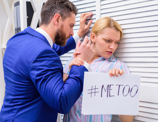 Prejudice office. Manager putting his hand on the shoulder of his secretary, at the office. Movement against sexual harassment. Woman showing a note with the text me too.