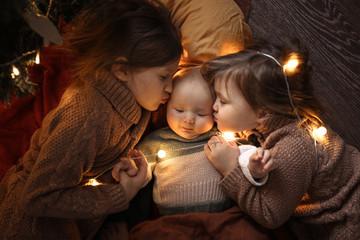 Older sisters hug baby,child 6 months lies sibling