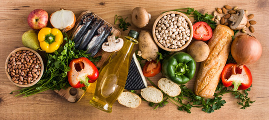 Healthy eating. Mediterranean diet. Fruit,vegetables, grain, nuts olive oil and fish on wooden table. Top view. Panoramic view Wall mural