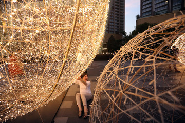 A woman poses for a picture in front of Christmas decoration at Iconsiam shopping mall in Bangkok