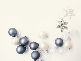 White and blue Christmas baubles on white background. Flat lay photo, copy space