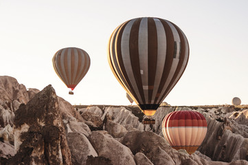 Goreme, Cappadocia, Turkey . Top view of colorful hot air balloons flying over the Red valley on sunrise.