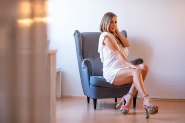 Sensual photo of a mature woman in a white dress while sitting and posing on a chair in a modern apartments living room.